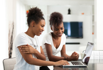 African American student girls using a laptop computer - black p. Female, home.