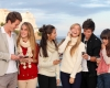 Group of happy smiling teens, kids, texting and calling with mobile or cell phones.
