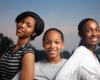 Three beautiful smiling teenage African American girls outdoors